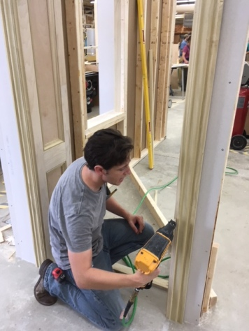 Me adding casing to a curved, paneled doorway I built.